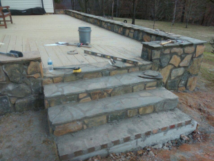 Rock wall around wooden deck with steps