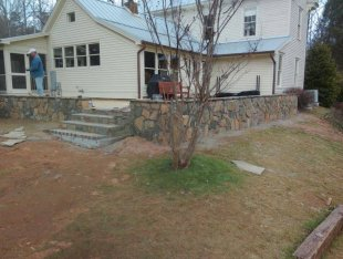 Wooden deck with stone wall and steps